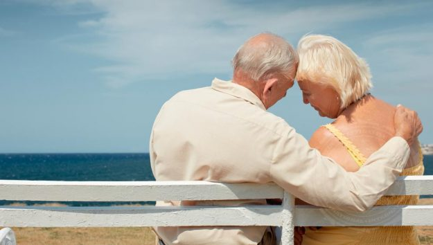 Two senior citizens on a bench, image featured in an article about avoiding senior abuse