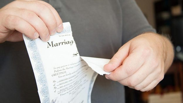 A victim of divorce tears his marriage license. This file is licensed under the Creative Commons Attribution 2.0 Generic license. Flickr author: Cordell Cordell.